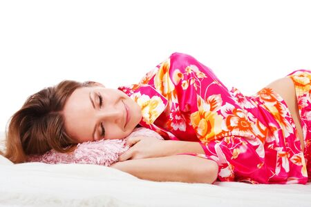 Picture of a sweet young girl in pink pajamas which sleeping on bed photo