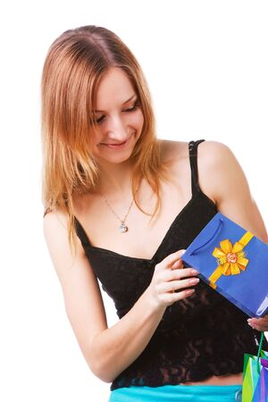 Picture of a beautiful young lady which looking into packets with a gift on white background. photo