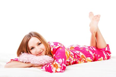 Picture of a sweet young girl in pink pajamas on bed photo