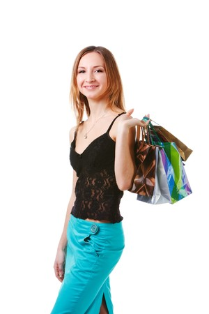 after shopping: Picture of a charming young lady in blue skirt with packets after shopping on white background. Stock Photo
