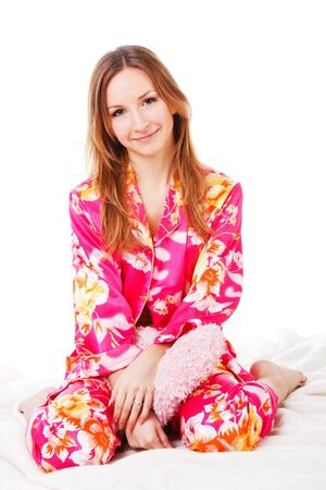 Picture of a sweet young girl in pink pajamas on bed Stock Photo - 7067766