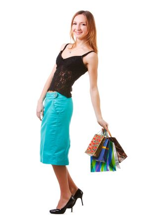 Picture of a charming young lady in blue skirt with packets after shopping on white background. photo