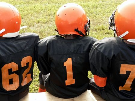 photo of little league football players sitting on a sidelines bench awaiting their turn to play. Stockfoto