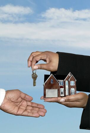 アフリカ系アメリカ人を示す住宅販売の不動産市場の概念写真家とキー転送を引き渡します。クリッピング パスが含まれます。