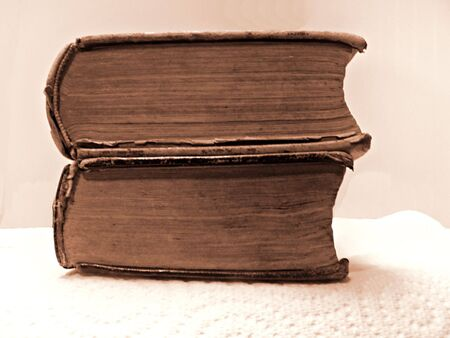 sepia tone photo of two antique books stacked up.
