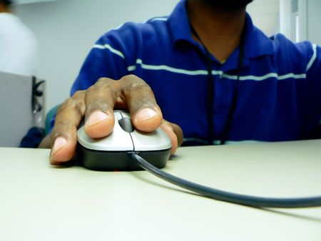 close up photo of a african american workers hand on a computer mouse while sitting at his desk Stok Fotoğraf
