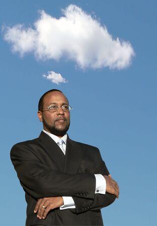 彼の頭の上に雲と深い思考のアフリカ系アメリカ人実業家の写真 写真素材