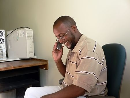 mobilephones: photo of a African-American man talking on cellphone at work