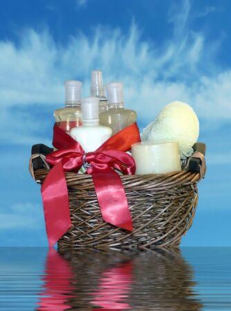 giftbasket: foto van een volledige van het bad accessoires met geïsoleerd op een blauwe hemel achtergrond met bezinning in water cadeau mandje Stockfoto