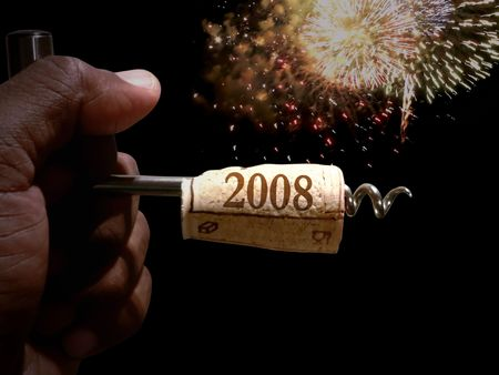 cork screw: hand holding a cork screw just pulled from a bottle of wine to celebrate new years eve
