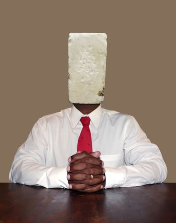 stubborn and think headed businessman personality concept photo manipulation depicting a brick for a head sitting at a desk ready for a meeting