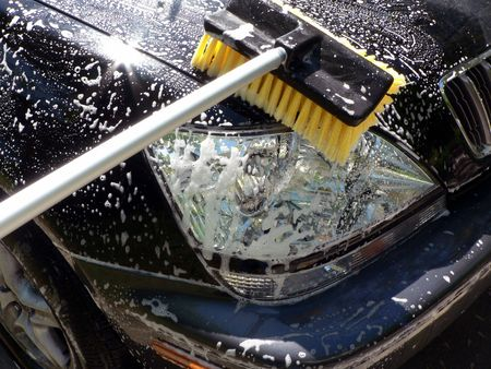 suv's front end being washed with a brush
