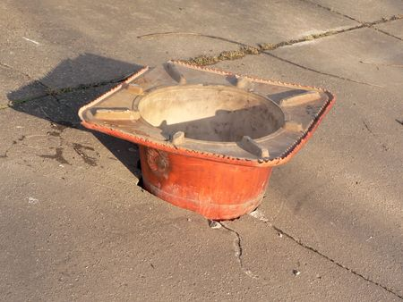 pothole: photo of a construction cone filling a pothole in a city sidewalk