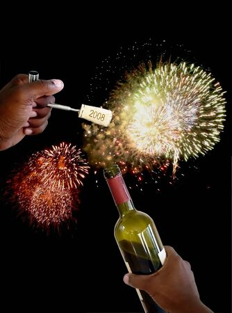 cork screw: hand holding a cork screw just pulled from a bottle of wine to celebrate new years eve with exploding fireworks Stock Photo