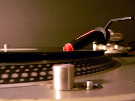 photo of dj turntable needle on record with the focus on the needle illuminated under party lights.