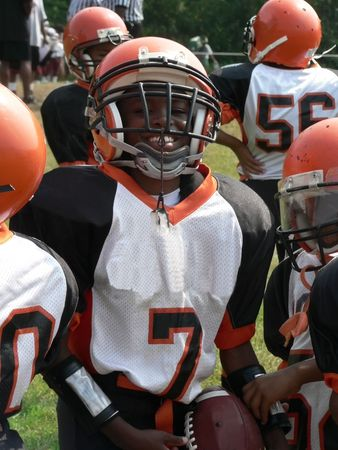 photo of little league football players sitting on a sidelines bench awaiting their turn to play. Stock Photo - 2180126