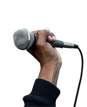 白い背景の上のボーカル マイクを握っている手の写真