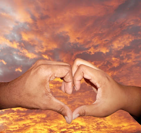close up photo of a African American male and female hands forming a heart shape to symbolize love and Valentines Day photo