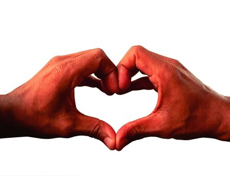 close up photo of a African American mans hands forming a heart shape to symbolize love and Valentines Day photo