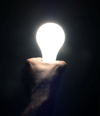 photo of idea concept showing a hand holding a lightbulb