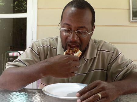 hombre comiendo: foto de un hombre African American comer un s�ndwich de chile para perros calientes en un patio cubierta