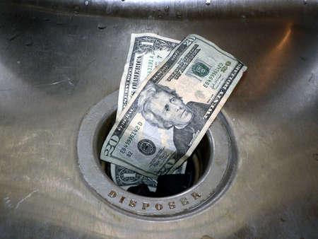 spending money: concept photo of money going down the rain