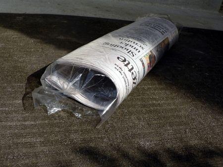 doorstep: newspaper lying on front doorstep in a protective bag Stock Photo