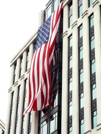 tribute: United States flags, hung during a cloudy day, on the front side of buildings in Arlington, VA as a memorial to pay tribute to the victims and heros of 9-11. Stock Photo