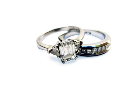 photo of a diamond & platinum wedding ring isolated on a white background with the focus on large diamond