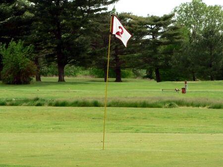 Foto van een wit vlag op een putting green van een golfbaan