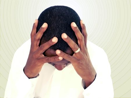 aggravated: african american man holding his head as if under stress Stock Photo