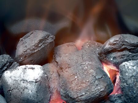 smolder: close up view of smoldering charcoal  in flames for use in a barbecue grill.
