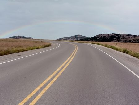 a road going through the Wichita Mountains of Oklahoma with a rainbow in the background Stok Fotoğraf