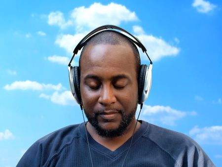 forty something: a isolated photo of a forty something year old african american man wearing headphones while listening to music