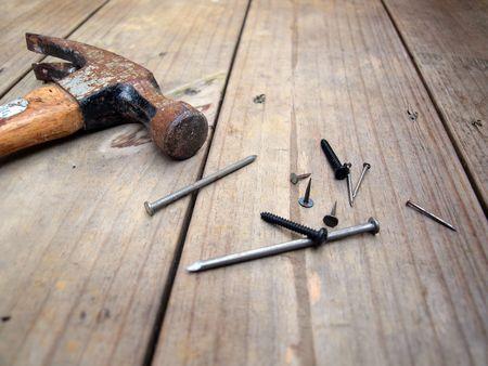 the hammer: Un martillo de clavos de edad, tornillos y clavos de madera, vigas de madera en cubierta. Foto de archivo