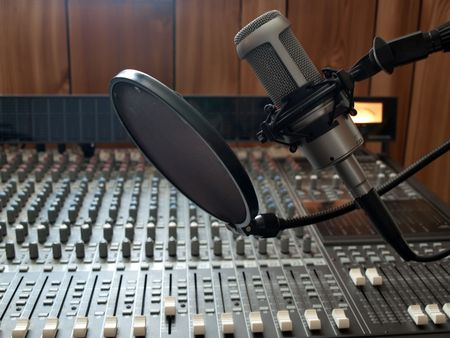 recording studio: a studio vocal microphone over a mixing board console Stock Photo