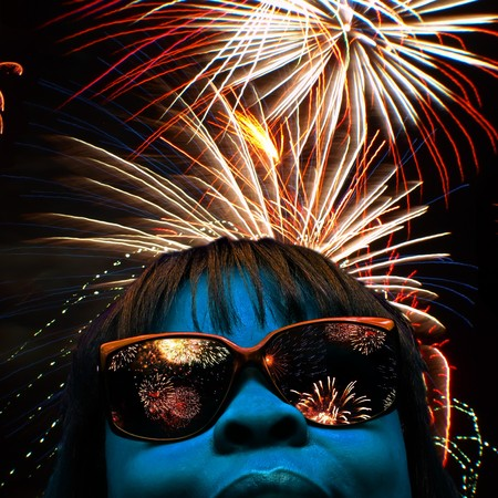 stylized facial portrait of a blue faced female with fireworks over head and reflecting off her shades