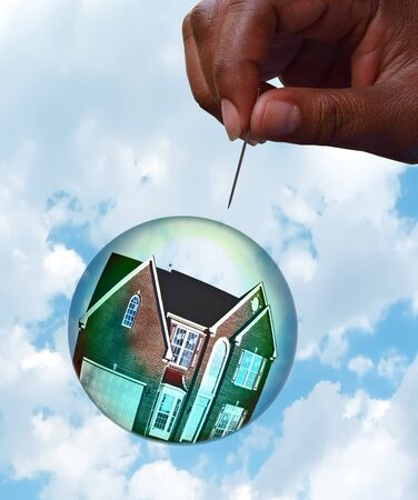 Housing market bubble burst concept photo with composition of home floating in a bubble towards a hand holding a pin depicting the fragility of the housing market. The house photo has been altered from its original appearance!