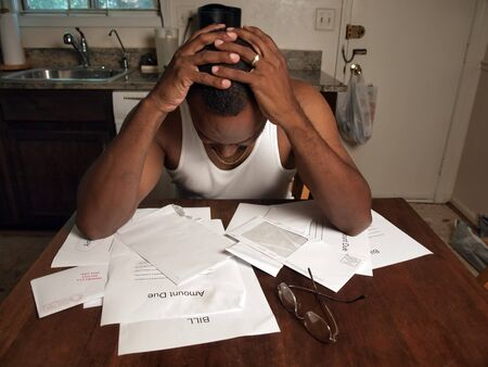 african american man holding his head as if under stress of his financial debt Stock Photo