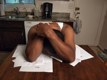 african american man holding his head as if under stress of his financial debt photo