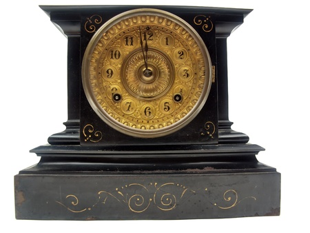 A black and gold antique mantle clock with the minute hand about to strike 12 o-clock isolated on a white background photo