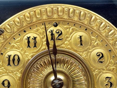 Close up of the minute hand of a black and gold antique mantle clock about to strike 12 o-clock. photo