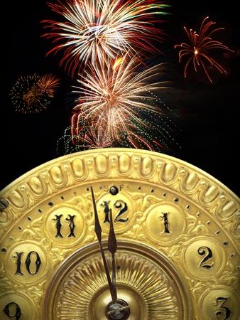 背景に花火で新年を開始する 12 o クロック真夜中のストライキを約アンティーク時計の文字盤の分針のクローズ アップ。
