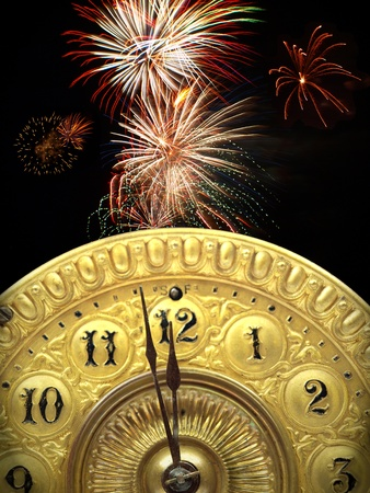 Close up of the minute hand of a antique clock face about to strike 12 o-clock midnight to start the new year with fireworks in the background.