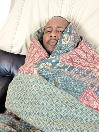 cropping: A african american man bundled under a blanket while sick. copy and cropping space included. Stock Photo