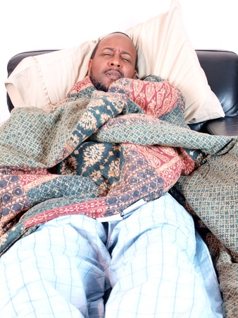 A african american man bundled under a blanket while sick. copy and cropping space included. Stock Photo