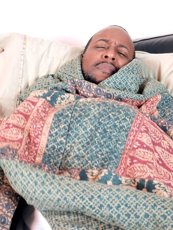 A african american man bundled under a blanket while sick. copy and cropping space included. photo
