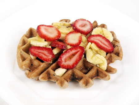 a Belgian waffle with slices of banana and strawberries on a white plate 版權商用圖片 - 12639693