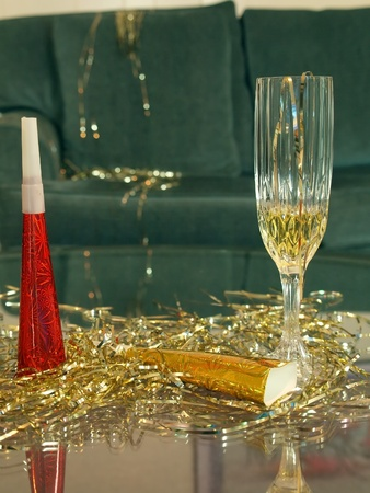 silver flute: new years eve celebration concept of a background with champagne flute, party favor, and glitter on a glass table in the foreground Stock Photo