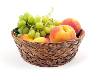 fruit basket: fruit basket of peaches and grapes on a white background